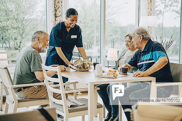 Lächelnde junge Gesundheitshelferin serviert älteren Männern und Frauen  die am Esstisch sitzen  Frühstück