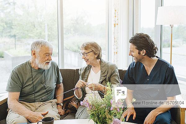 Lächelnder Mann und lächelnde Frau im Ruhestand unterhalten sich mit dem männlichen Betreuer  während sie auf dem Sofa am Fenster des Pflegeheims sitzen