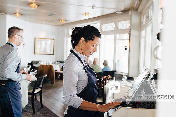 Frau benutzt Computer im Restaurant