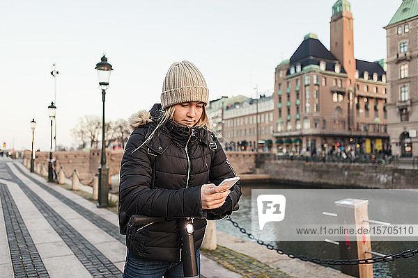 Teenager-Mädchen benutzt Smartphone  während sie auf einem E-Scooter am Kanal in der Stadt steht