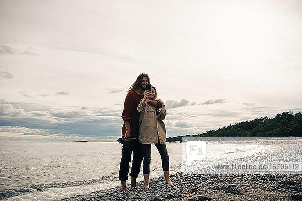 Pärchen in voller Länge am Strand mit Smartphone am Strand gegen den Himmel