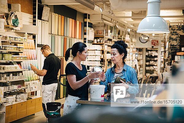 Verkäuferin zeigt dem Kunden im Baumarkt eine Farbdose