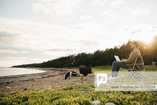 Mittelgroßer erwachsener Mann benutzt Laptop  während er am Strand am Ufer gegen den Himmel sitzt