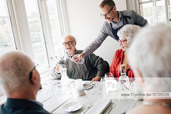 Eigentümer serviert Wasser an lächelnden älteren Mann  der mit Freunden im Restaurant sitzt