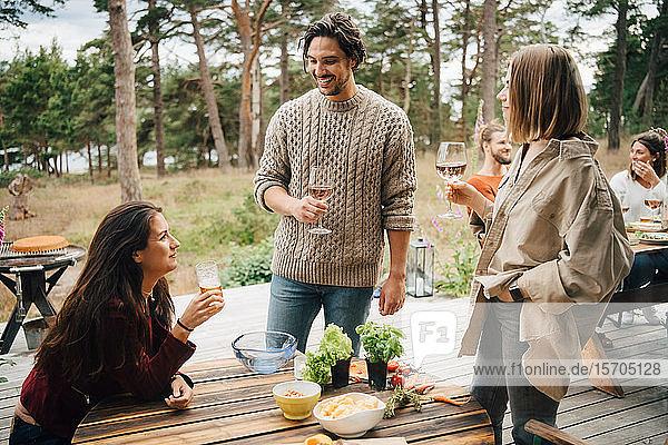 Lächelnde Freunde genießen Getränke während eines Gesprächs während einer Gartenparty im Hof