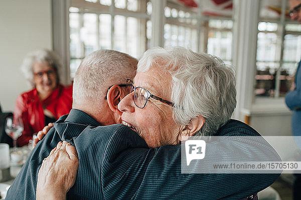 Älterer Mann umarmt Frau  während er im Restaurant sitzt