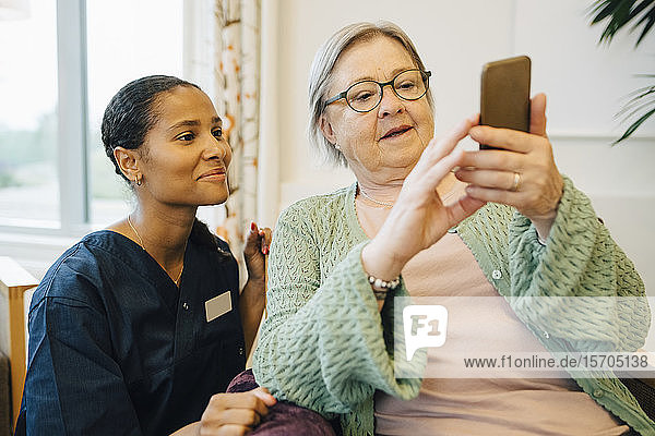 Lächelnde Betreuerin schaut ältere Frau an  die im Pflegeheim ein Mobiltelefon benutzt