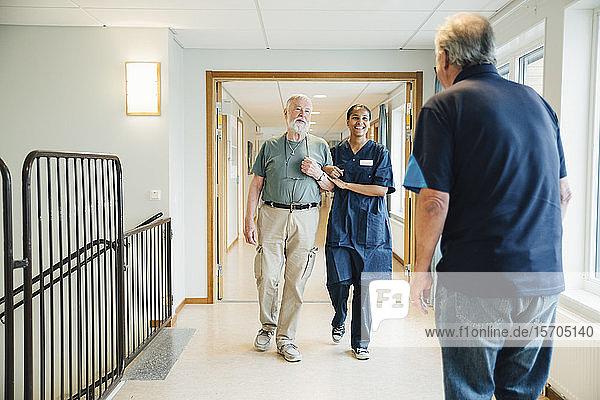 Älterer Mann geht Arm in Arm mit einer Krankenschwester  während er einen Freund in einer Gasse im Pflegeheim betrachtet