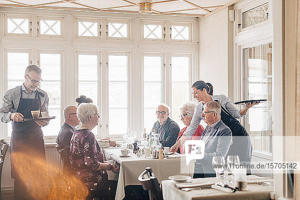 Besitzer servieren Kaffee an Freunde und Freundinnen  die am Restauranttisch sitzen