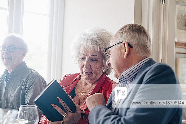 Ältere Frau unterhält sich mit einem männlichen Freund  während sie im Restaurant ein Buch in der Hand hält