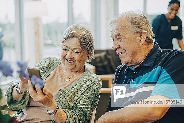 Lächelnde ältere Frau teilt Smartphone mit Mann  während sie im Altersheim sitzt