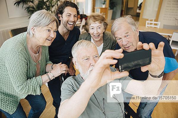 Behinderter älterer Mann nimmt Selbsthilfe mit Freunden und Krankenpfleger im Altenheim