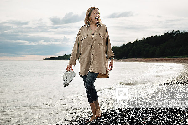 Cheerful young woman holding shoes while walking at beach against sky