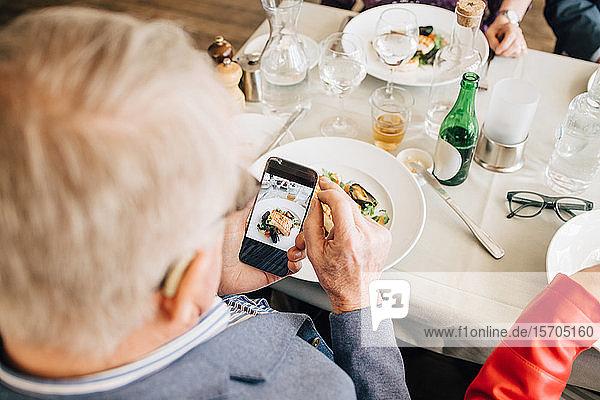 Älterer Mann fotografiert Essen im Restaurant