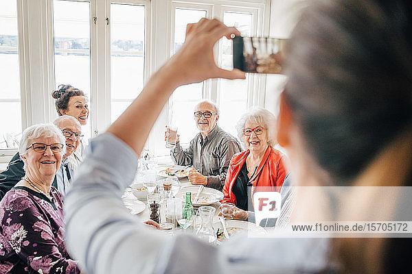 Eigentümer klickt auf Foto von älteren Freunden  die im Restaurant sitzen