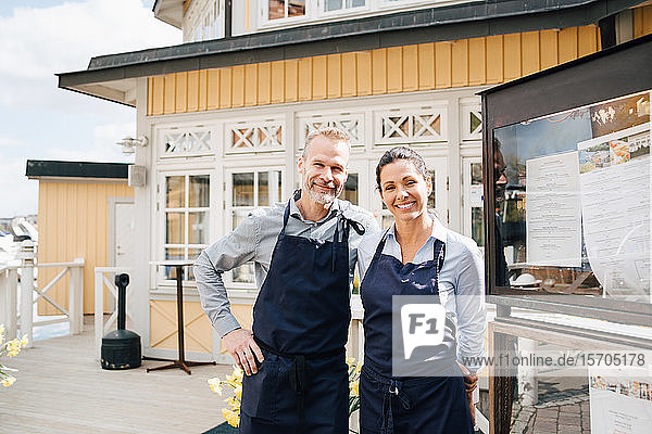 Portrait of smiling owners outside of restaurant