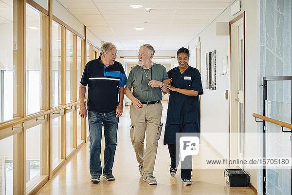 Älterer Mann geht Arm in Arm mit einer Krankenschwester  während er mit einem Freund in einer Gasse im Pflegeheim spricht