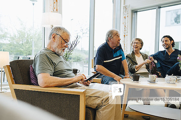 Senior man using smart phone while sitting with newspaper on armchair by friends and caretaker at elderly nursing home