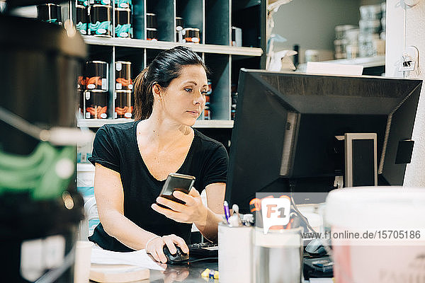 Sales woman using computer while holding mobile phone in store