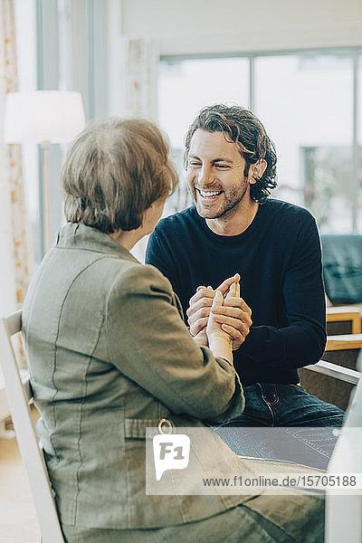 Lächelnder Mann hält Hände,  während er mit Großmutter im Altenpflegeheim spricht
