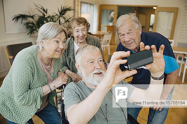 Behinderter älterer Mann nimmt sich mit Freunden im Altersheim ein