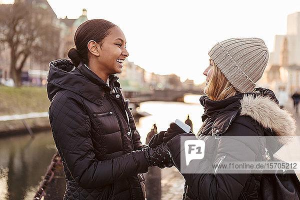 Glückliche Freundinnen halten sich im Winter bei einem Gespräch in der Stadt an den Händen
