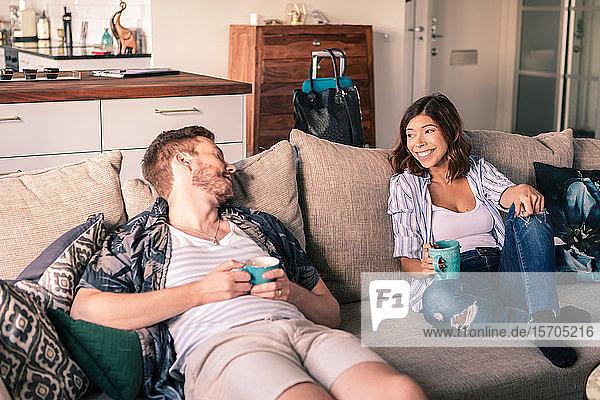 Paar unterhält sich beim Kaffeegenuss auf dem Sofa in der Wohnung