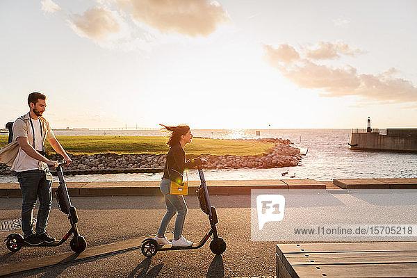 Ehepaar in voller Länge genießt beim Fahren mit Elektrorollern auf der Straße am Meer gegen den Himmel