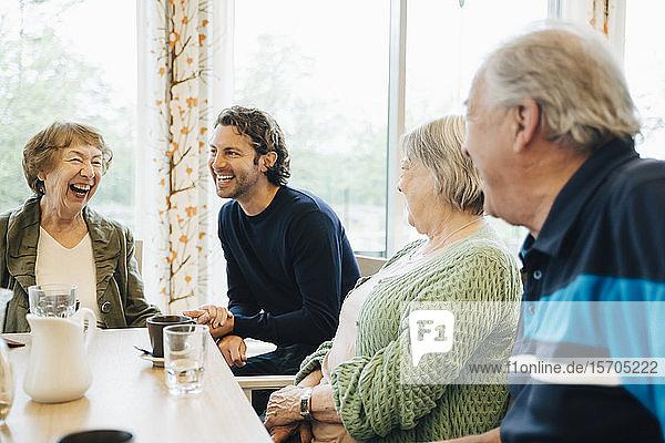Lächelnder Mann besucht seine Großmutter und ihre Freunde im Altersheim