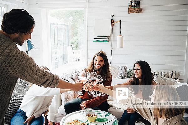 Männliche und weibliche Freunde stoßen bei Tisch in einer Hütte mit Weingläsern auf das Essen an