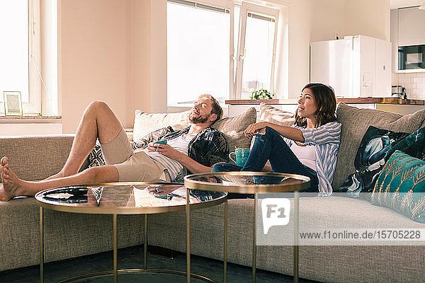 Ehepaar genießt Kaffee  während es sich auf dem Sofa in der Wohnung ausruht