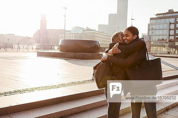 Multiethnische Teenager-Freunde  die sich bei der Begrüßung in der Stadt im Winter schrittweise umarmen