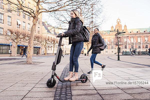 Freundin betrachtet Teenager-Mädchen  das im Winter auf einem E-Scooter auf der Straße in der Stadt fährt