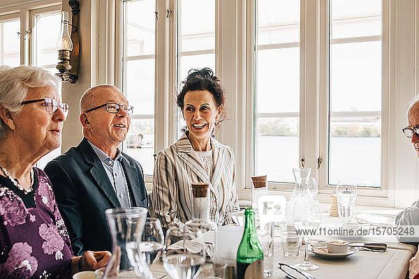 Ältere Freunde lächeln  während sie im Restaurant sitzen