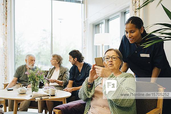 Pensionierte ältere Frau teilt Smartphone mit junger Krankenschwester bei Gemeindeeinsätzen