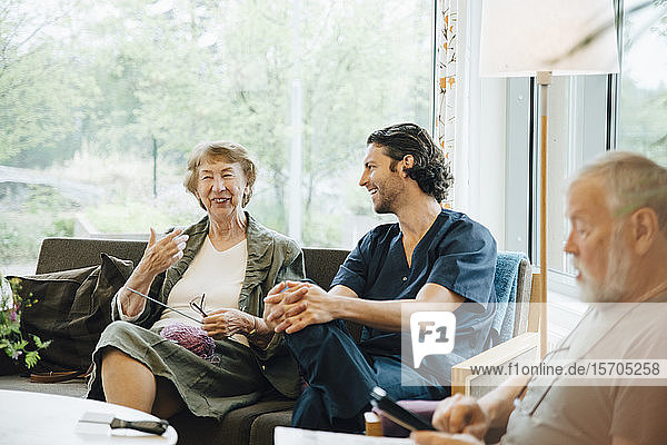 Smiling senior woman talking with male nurse sitting on sofa against window at nursing home
