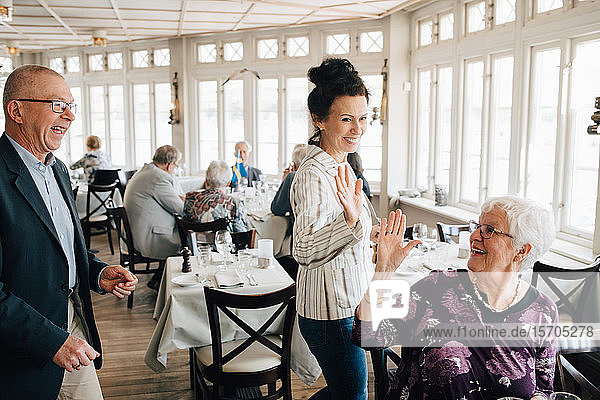 Ältere Freunde geben High-Five im Restaurant
