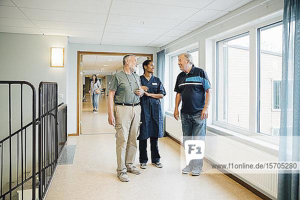 Älterer Mann in voller Länge Arm in Arm mit Krankenschwester im Gespräch mit Freundin auf der Gasse im Pflegeheim