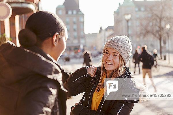 Lächelndes Teenagermädchen unterhält sich im Winter mit Freundin in der Stadt