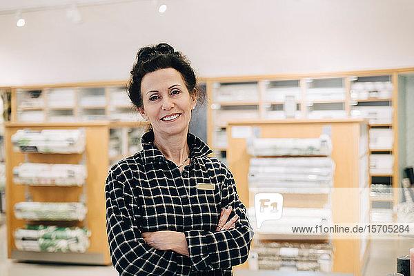 Porträt einer lächelnden Verkäuferin mit verschränkten Armen im Laden stehend