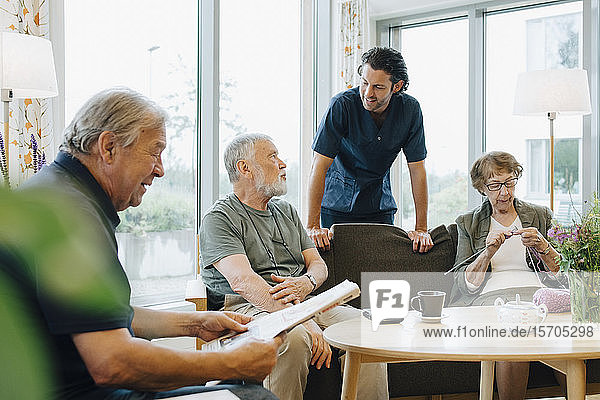 Male healthcare worker talking to senior man sitting on sofa amidst friends at retirement home