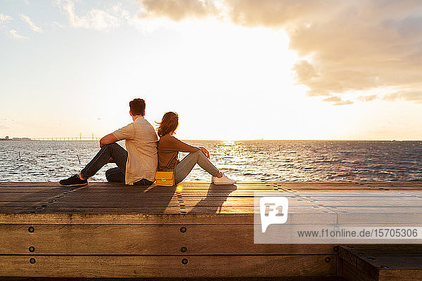 Ehepaar sitzt in voller Länge auf einem Sitz am Meer gegen den Himmel bei Sonnenuntergang