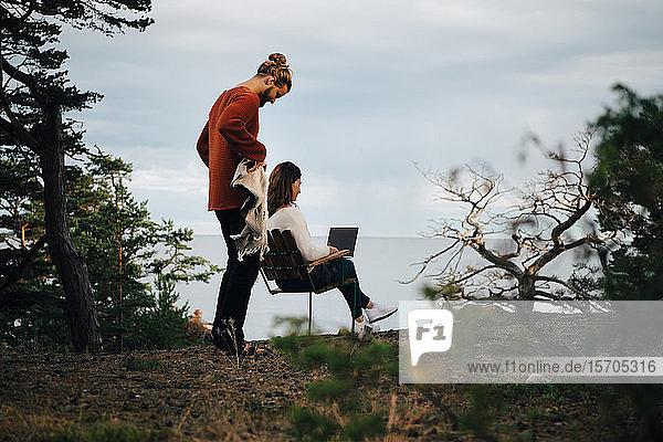 Mann hält Decke  während Frau mit Laptop im Wald gegen Himmel