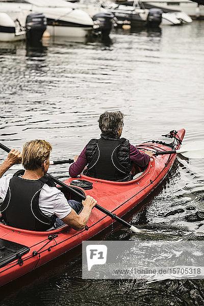 Rückansicht einer älteren Frau und eines älteren Mannes beim Kajakfahren auf See während eines Trainingskurses