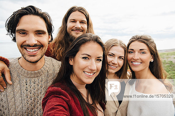 Porträt glücklicher Freunde gegen den Himmel