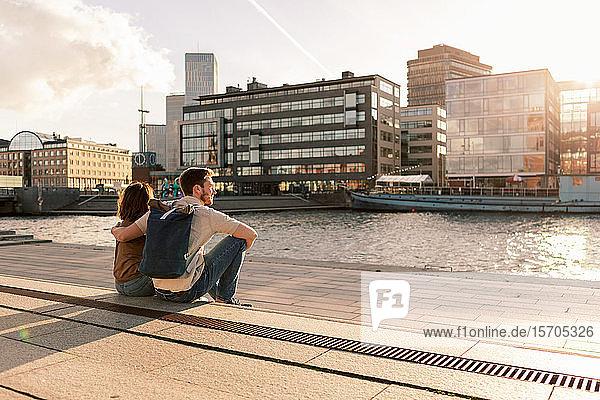 Ein Paar sitzt auf der Promenade und schaut auf einen Fluss in der Stadt