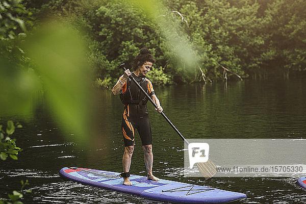 Lächelnde ältere Frau in voller Länge beim Paddelbootfahren auf See während des SUP-Kurses