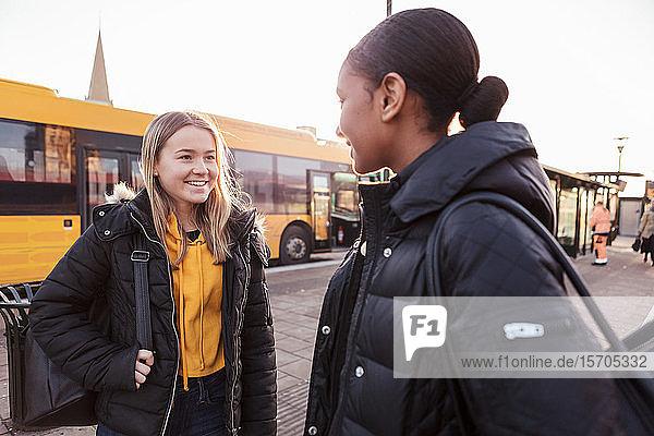 Lächelnde Freunde unterhalten sich  während sie in der Stadt gegen den Bus stehen