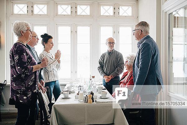 Ältere Frau sitzt am Restauranttisch  während männliche und weibliche Freunde am Tisch stehen