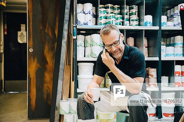 Salesman using phone while sitting on stool in storage room
